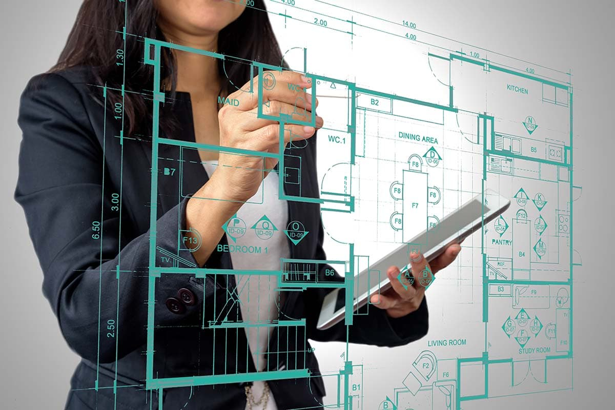 Woman drawing out blueprint for a complete home assessment on clear glass screen
