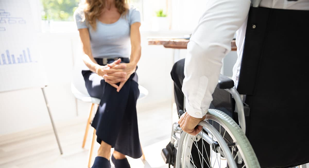 Woman sitting across from an injured worker in a wheelchair